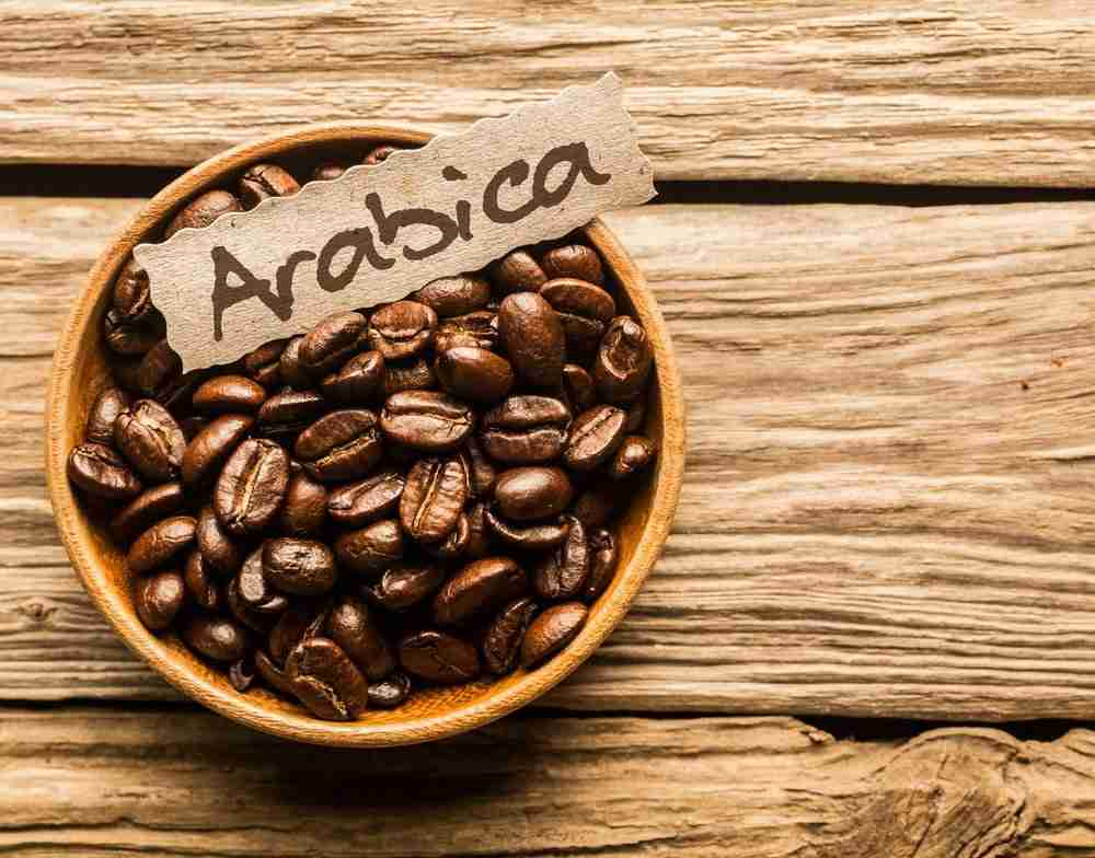 """A bowl of arabica coffee beans with a label saying """"arabica"""""""
