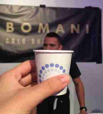 Holding up a paper cup in front of the CEO of Bomani cold buzz. One of the booths in the New York City Coffee Festival.