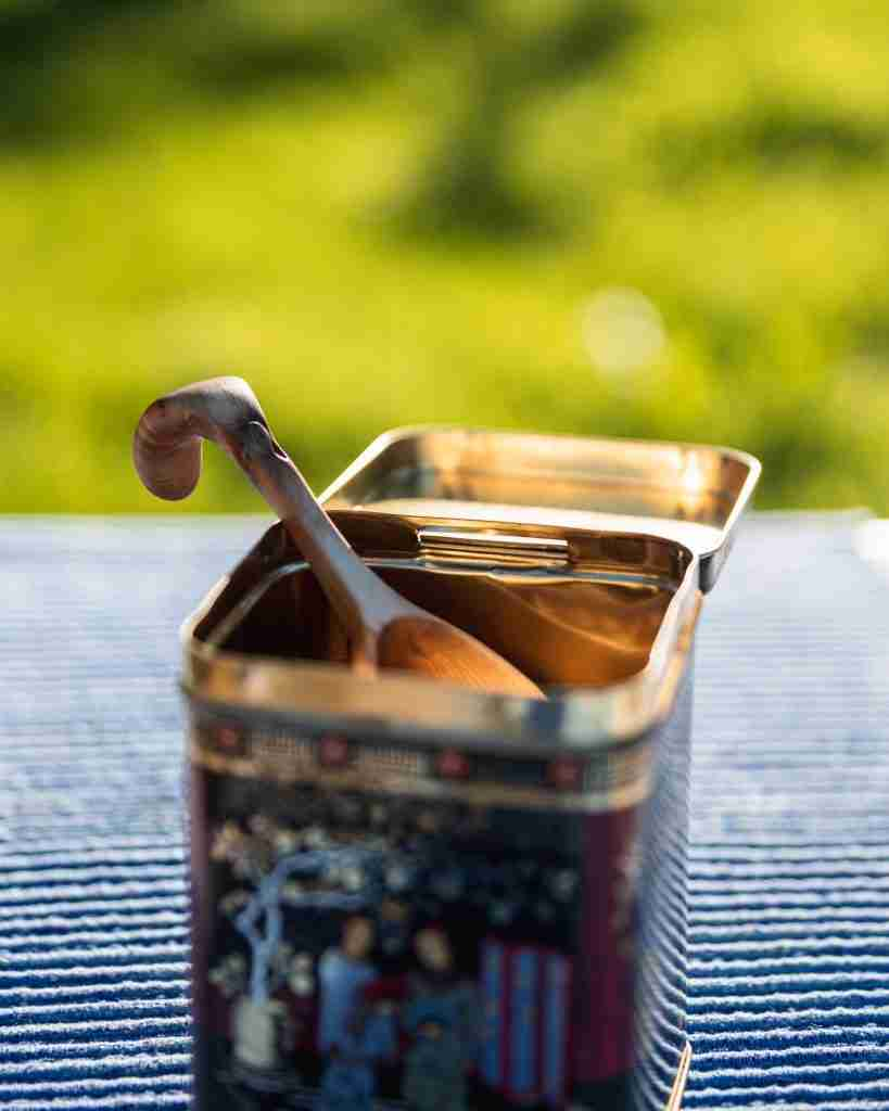 Properly storing your coffee beans by putting them in an airtight container with a spoon.