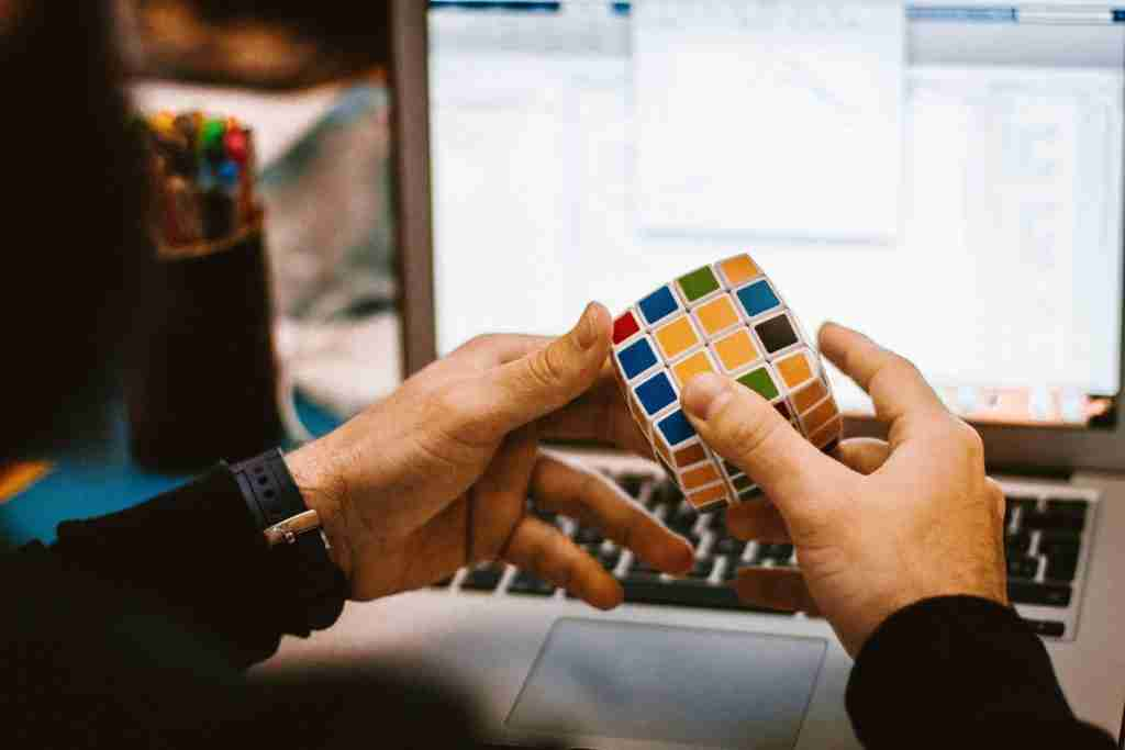 hands playing with a Rubiks cube in front of a work laptop