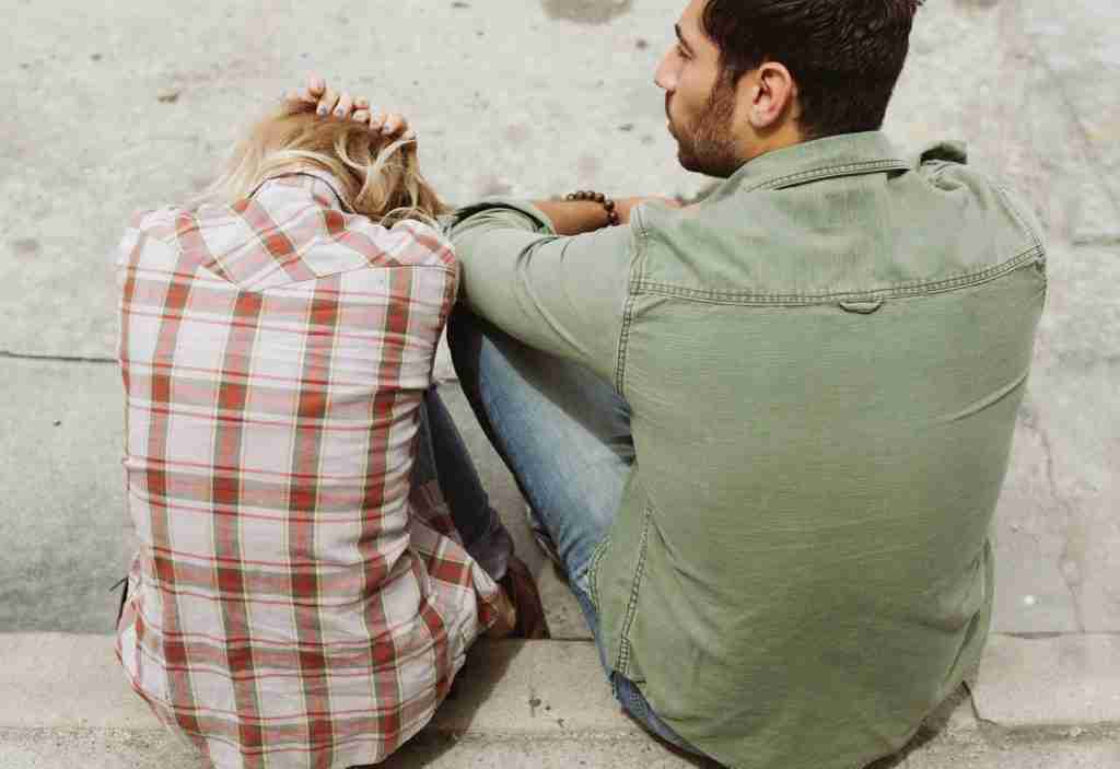 Man in green button down and woman. in plaid sitting next to each other.